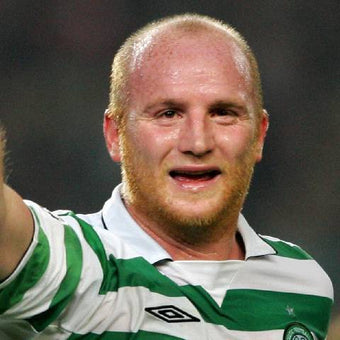 Photograph of footballer John Hartson in his green and white Celtic kit, waving to the crowd during a match