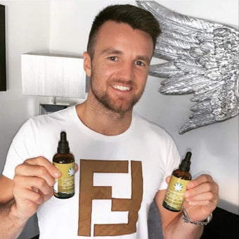 Photograph of boxer Anthony Fowler in a white tshirt, holding two bottles of Supreme CBD Oil