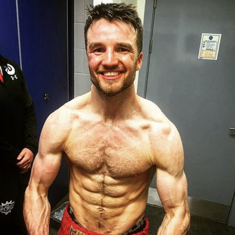 Photograph of boxer Anthony Fowler flexing after a macth