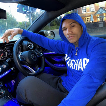 Photograph of Conor Ben in a blue hoodie and black jeans, sat at the wheel of his car