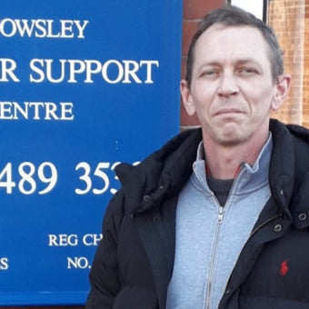 Photograph of ambassador Shaun Walsh in front of a blue Support Centre sign
