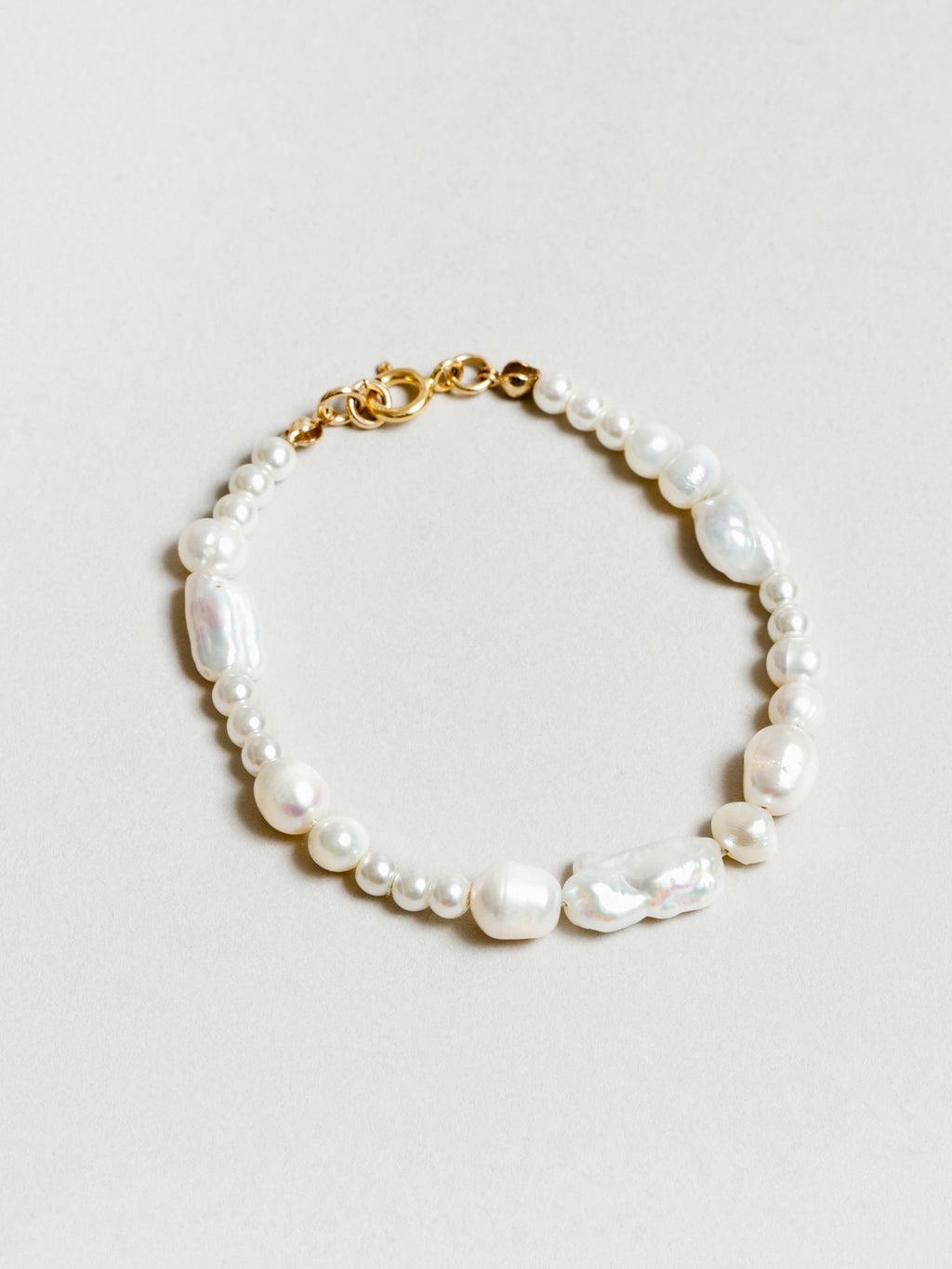 Pearl bracelet with varied sized pearls and gold clasp.