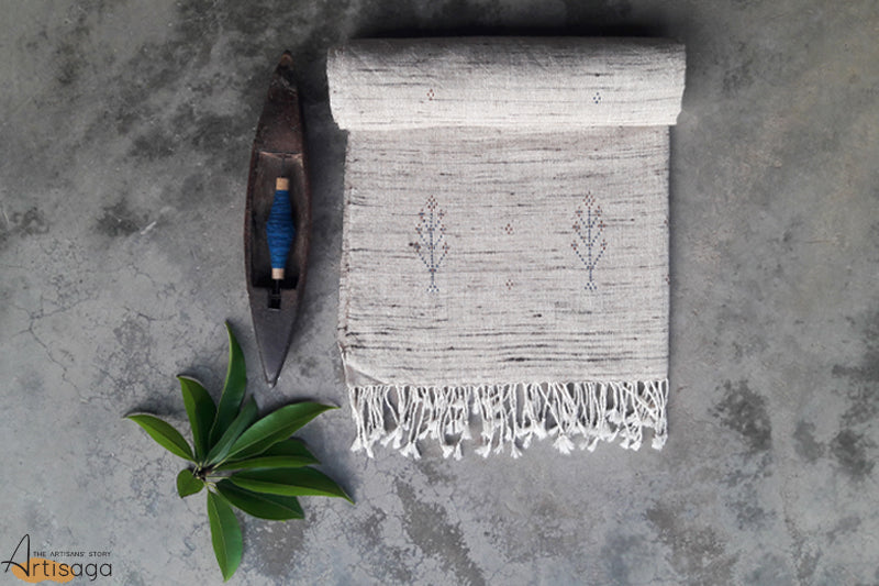 A traditionally handcrafted cotton and tussar silk stole from Kutch, Gujarat.   An elegantly hand crafted stole of the Tangasia community, Gujarat. The off-white colour with black melange effect and playful tassels gives this stole a unique look. The product is woven with intricate detailing inspired by nature (jhaad). Pair this delicate and simple piece with a plain white kurta and black churidaar to add to your aesthetic appeal.