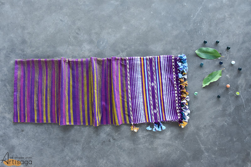 An intricately hand woven Gicha tussar silk stole from Kutch, Gujarat.   A fascinating stole woven in the combination of cool toned purples with a hint of ochre, white and olive green. The miri border along with colourful tassels add an eccentric touch to this piece. Pair this handcrafted stole with a plain black canvas and rustic jewellery to conquer millions of hearts.