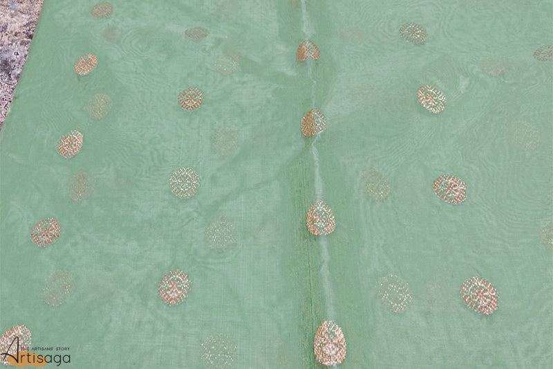 A diligently hand woven 100% Chanderi silk saree from Madhya Pradesh.   An ethereal sea green hand woven chanderi saree is traditional yet modern in design. A shimmering thick zari border is complemented with well intricate work on the motifs. Even though heavy in work, the saree is extremely light weight and wearable for all Indian festivities.