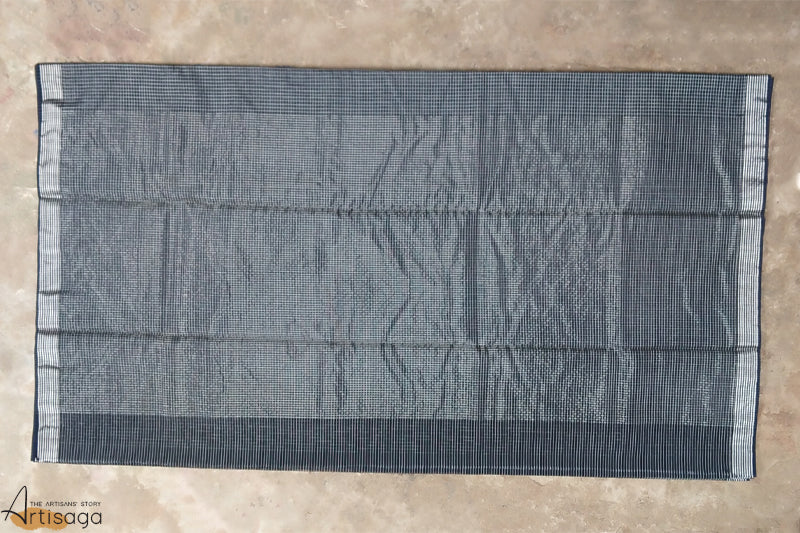 An ethereal handwoven Chanderi cotton silk saree from Madhya Pradesh.   This unique Chanderi saree is handcrafted by the untiring artisans of Madhya Pradesh. The bold black background has intricate checkered patterns woven all over the saree. The striped zari border makes it a distinctive piece. Drape this six yards of elegance with a bold red lip and bouffant hairstyle for a retro look.