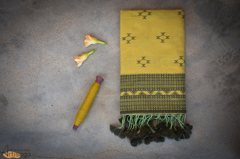 A traditionally hand woven 100% cotton stole from Kutch, Gujarat.   Dusty yellow yarns along with nature's very own green is interwoven to form stripes. This kachchhi hand woven stole has chaumukh motifs laid out in a diamond pattern with traditional miri borders. This simple yet sophisticated piece is further uplifted with monochrome tassels. This unique piece will make any simple attire look classy.