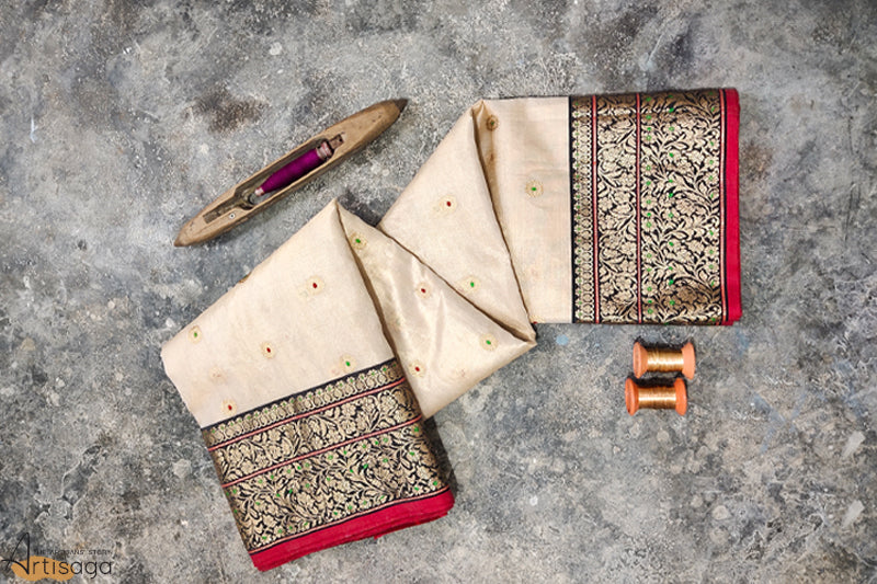A diligently hand woven Chanderi tissue silk saree from Madhya Pradesh.   An off-white Chanderi saree complemented with hints of red, black and green is the perfect example of a traditional evergreen piece. The work on the border is heavily detailed and intrinsic yet the saree possesses a delicate soft quality. The motifs are of a gleaming golden zari ethereal to look at. A bold red lipstick along with this traditionally draped saree makes a statement on its own.