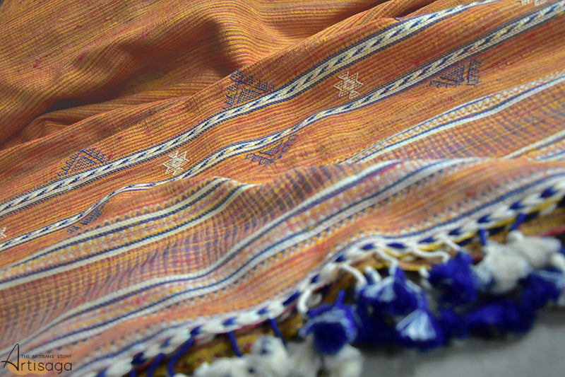 An intricately hand woven Gicha tussar silk stole from Kutch, Gujarat.   This subtle yet bright hand woven stole is a perfect blend of traditions with a modern twist. Simple stripes created by the earthy toned colours are the prime features of this stole. The traditional chaumukh motif complemented with bouncy white and blue tassels makes this stole one of a kind. Drape this exquisite stole with your classics to enhance your look for casual and work meetings.
