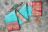 A diligently hand woven 100% Chanderi silk saree from Madhya Pradesh.   This beautiful fusion of sky blue and blooming red colour has been handwoven by the artisans of the Chanderi community. The saree is heavy in design yet extremely light in nature. The colours complement each other so well that they create an impact at first sight. This saree is best paired with a bold red lip.
