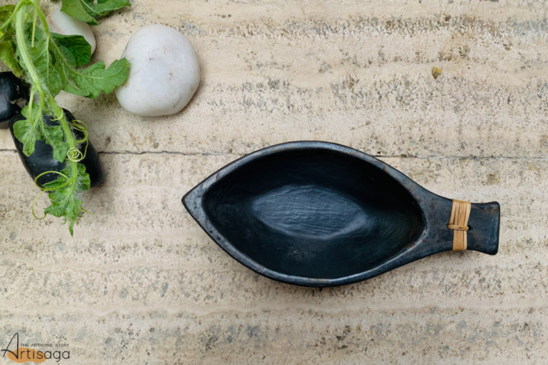 An eco-friendly earthenware clay nut bowl of Longpi pottery from Manipur.   This aesthetically unique handcrafted bowl in the shape of a nut is made with 100% clay. It is shiny, smooth and sleek at the same time. Not only is it multipurpose, it is also durable and can be used as an item of decor on special days.