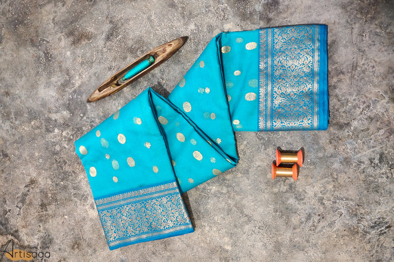 A diligently hand woven 100% Chanderi silk saree from Madhya Pradesh.   A hand woven Chanderi saree replicating the essence of monsoon with different shades of blue. Intricate zari and minakari work on the border, embellished with traditional motifs along the saree signifying nature, portrays the trails of leaves and flowers. This beautiful saree when paired with minimal jewellery is the epitome of grace.