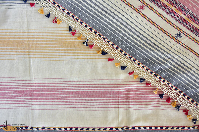 An intricately hand woven 100% cotton saree from Kutch, Gujarat.   The striped woven saree is made by intermixing various coloured yarns into a collective pattern. The netted pattern along with the colourful tassels on the pallu add an altogether different tangent to this enchanting piece. The contrasting colors of white, black, red and yellow add an additional touch to the overall look of the fabric. Pair this lightweight saree with your comfiest footwear for a great everyday look.