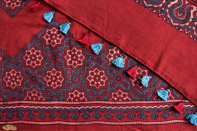 An enchanting hand block printed mul cotton saree from Ajrakhpur, Gujarat.   Hand block printed with ethnic yet contemporary motifs, this saree is a go to for every buyer. With blended natural colours of red and peach, the navy blue circles and geometrical shapes add vibrance to the piece. The beautiful printed floral pattern complemented by red and blue tassels elevates the experience of this saree.