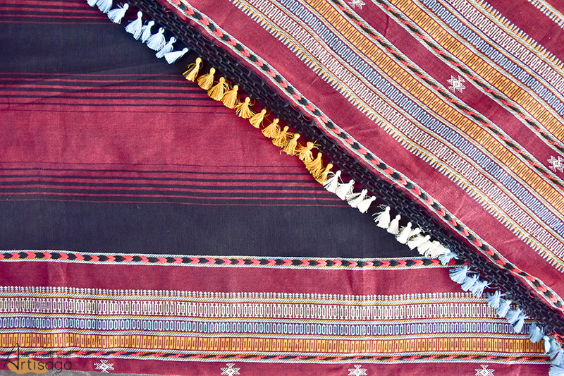 An intricately hand woven 100% cotton saree from Kutch, Gujarat.   The saree is a unique piece with an extricate design well suited for festive occasions. The maroon colour with white motifs gives a royal look to the wearer. The broad orange border uplifts the feel of the saree and the white, yellow and blue parallel lines subtle up the extravagance of the saree. The multi coloured tassels at the pallu add a casual tint to the saree.