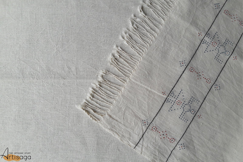 A traditionally handcrafted 100% organic cotton stole from Kutch, Gujarat.   Simplicity blended with precision and technique is the USP of this woven stole from the Kutch district of Gujarat. Little dana embellishments representing female figurines along with plain white tassels makes this piece one of a kind. An ikkat long kurta, ankle length pants and the added highlight of the stole makes an extraordinary statement.