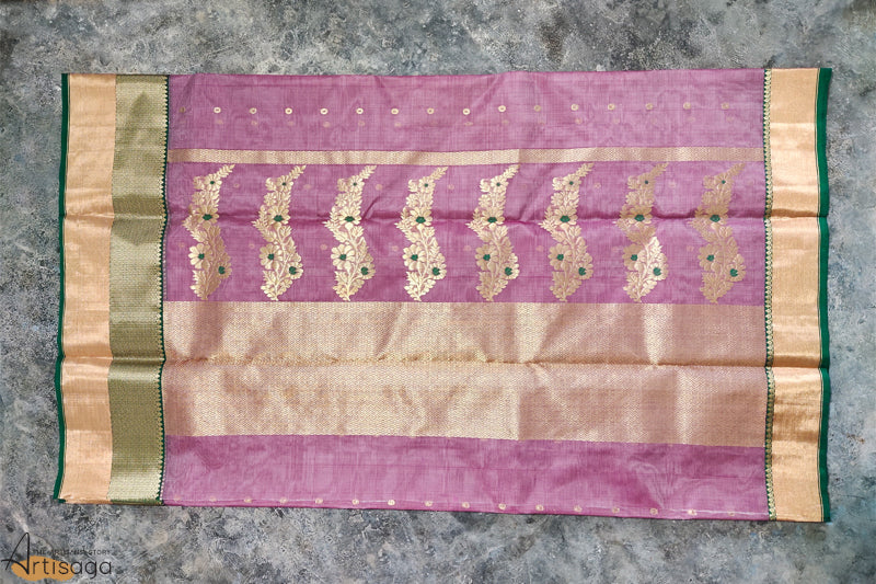 A diligently hand woven 100% Chanderi silk saree from Madhya Pradesh.   This unique onion pink coloured saree, hand woven using 100% silk yarns, is delicate and soft both in design and touch. The work on the khad motifs is intricate and subtle at the same time. The intricate dark green and zari border along the saree gives it an ethereal look. Style this regal piece with heavy jewellery and a traditional potli bag.