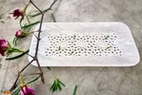 An intricately handcrafted alabaster stone tray from Agra.   This alabaster white tray is handcrafted with ethnicity and visual appeal. It is simple, delicate, sophisticated and charming to look at. Being multifunctional, it can be used both as a decorative item and serving plate. The simple jaali work displayed all along the tray adds a regal and majestic look to it. It is perfect for breezy mornings with a cup of tea and biscuits.