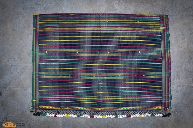 A traditionally hand woven 100% cotton saree from Kutch, Gujarat.   This unique combination of hand woven stripes and chequered pattern is a creation of Kutch weaving, a traditional practice inherited from the ancestry. The addition of pop colours of yellow, green and wine on the navy blue makes this formal saree livelier. The pallu is embellished with jali border and multicoloured tassels. Pair it with your statement jewellery and flaunt this classic piece from work to dinner.