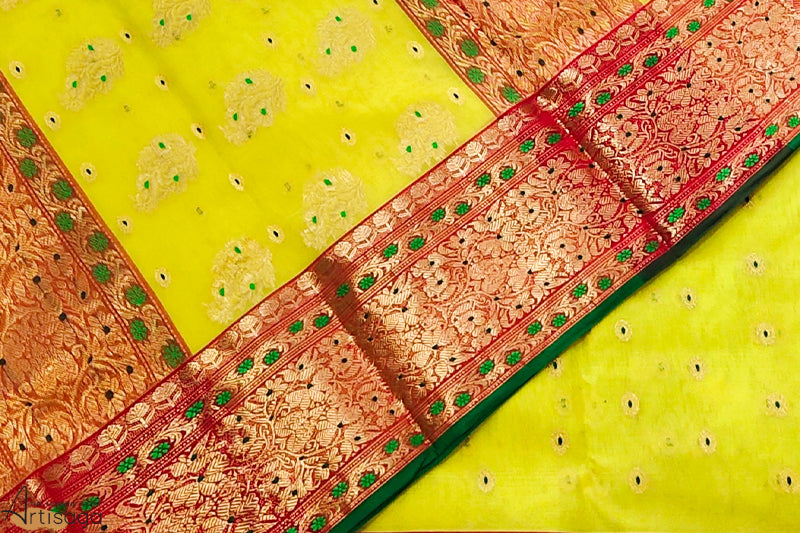 A diligently hand woven 100% Chanderi silk saree from Madhya Pradesh.   A bright yellow Chanderi saree with intricate green design and the detailed red border, strikes one's eye. The minakari work throughout the saree gives it a majestic look. This hand-woven saree is a perfect wear for traditional and ethnic festivities.