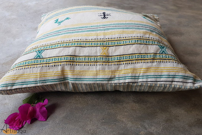 A traditionally hand woven 100% organic cotton pillow cover from Kutch, Gujarat.   A culturally designed pillow cover with a hint of modern touch to it. The Kutch community brings to you a well handcrafted piece with intricate yet detailed traditional motifs in various colours of teal, black and yellow on a plain white canvas. The striped pattern adds to its aesthetics and makes it perfect for enlivening the room.