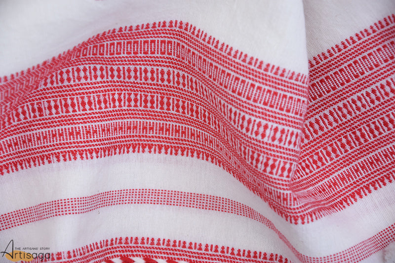 A traditionally hand woven 100% cotton stole from Kutch, Gujarat.   The serene beauty of this hand woven stole of the Kutch community is uniquely pleasing to the eye. The combination of red and white is simple yet unique in its own way. The aura of this piece is further magnified with the embellishment of traditional motifs and miri border. The addition of bouncy tassels to a plain canvas makes this piece fit for all occasions.