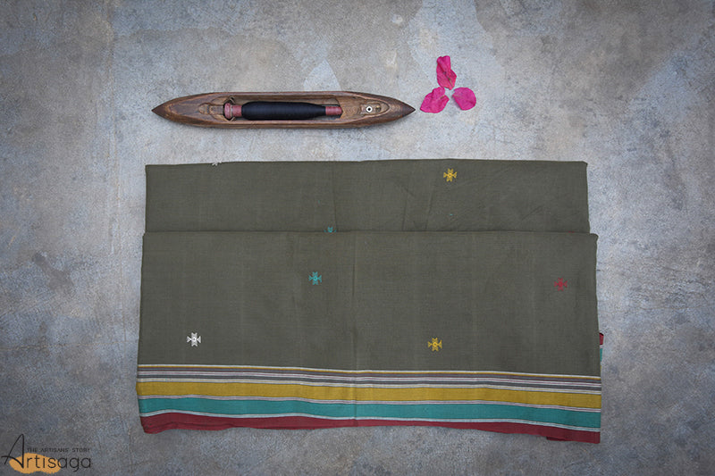 A traditionally hand woven 100% cotton saree from Kutch, Gujarat.   The unique colour combination of red, ochre and aqua on olive green makes this saree one of a kind. The intricate detailing with traditional kachchhi motifs throughout the saree brings forward the various cultures and beliefs of the Kutch community. The jali and the miri border along with the colourful tassels complement the overall look of the saree. This casual yet classy piece is suitable for all kinds of occasions.