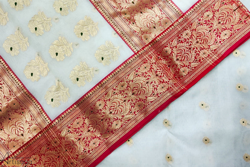 A diligently hand woven 100% Chanderi silk saree from Madhya Pradesh.   A rich and delicate hand woven white Chanderi saree is well complemented with a bold red border embellished with thick zari work. The subtle gilded motifs give it a sophisticated touch. A saree which is light in touch and feel, is one of the staple pieces to own.