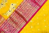 A diligently hand woven 100% Chanderi silk saree from Madhya Pradesh.   A traditional haldi coloured hand woven Chanderi saree complemented with a beautiful magenta zari border with hints of purple. The work on the border is intricate yet it is extremely light both in feel and look. The khad motifs are beautifully woven into the weft of the saree. Style this gleaming saree for poojas and wedding functions.