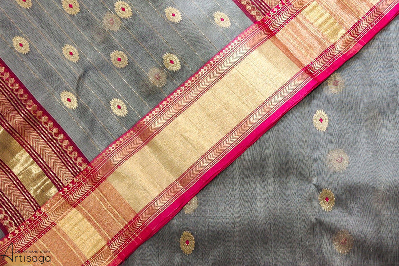 A diligently hand woven 100% Chanderi silk saree from Madhya Pradesh.   A modern take on a Chanderi saree with contemporary shades of grey and pink that complement each other so well. The design speaks of elegance with a traditional touch of the thick golden zari border. This sophisticated piece is stylish yet extremely light and wearable. Accessorise this handcrafted saree with contrasting pink or gold for a sumptuous look.