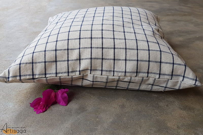 A traditionally hand woven 100% organic cotton pillow cover from Kutch, Gujarat.   A contemporary pillow cover set handwoven by the artisans of Kutch. It has a black checkered pattern on a contrasting white background. This neutral colour combination is a perfect match for all types of home decor.