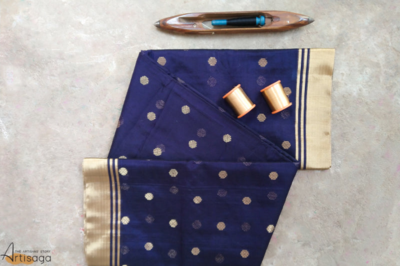 An ethereal handwoven Chanderi cotton silk saree from Madhya Pradesh.   This striking saree is handcrafted by the artisans of the Chanderi community. The rich navy-blue colour is well complemented with the gold motifs and zari border all over its spread. Despite the heavy work on the pallu, the saree is extremely light weight and wearable. Pair this beautiful saree with heavy tamba jewellery and an embellished jhola bag for your wedding festivities.