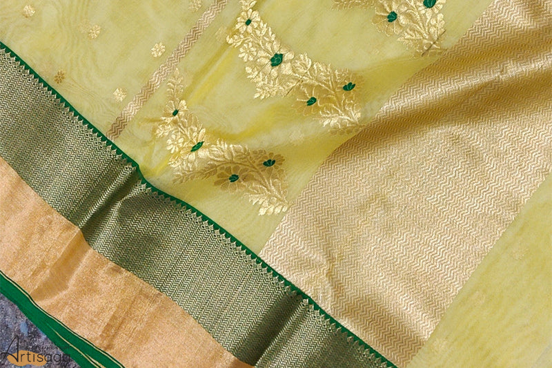 A diligently hand woven 100% Chanderi silk saree from Madhya Pradesh.   A lemon-yellow hand woven Chanderi saree is well complemented with a dark green and gold zari border. Delicate and soft both in design and touch, the work on the motifs is intricate yet subtle at the same time. An effortless and wearable saree, appropriate for all occasions.