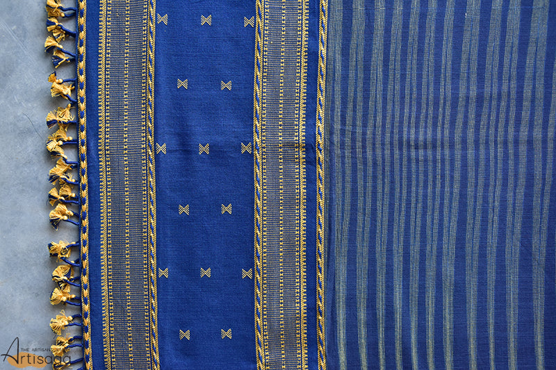 An intricately hand woven 100% cotton stole from Kutch, Gujarat.   The oxford blue and grey colours create a zigzag effect on the entire stole, widened at the ends and tapered in the centre. It is further upgraded with the braided like miri border of kutch, dotted stripes and yellow tassels along with the traditional kachchhi motif. Add a little pop to your simple yellow dress with this handwoven stole for a fun, festive look.