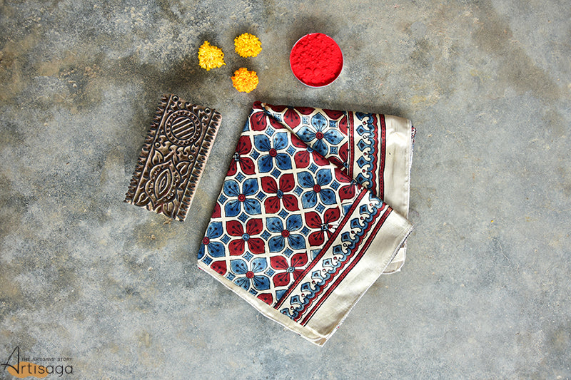 An exquisite hand block printed mashru stole from Ajrakhpur, Gujarat.   An elegant yet sophisticated hand block printed stole is the choice of all the age groups. The chic assortments of red and blue flowers accompanied by red parallel stripes elevates the experience of the stole. The bold motifs with intricate designs of Ajrakh makes it a winning piece for all occasions.