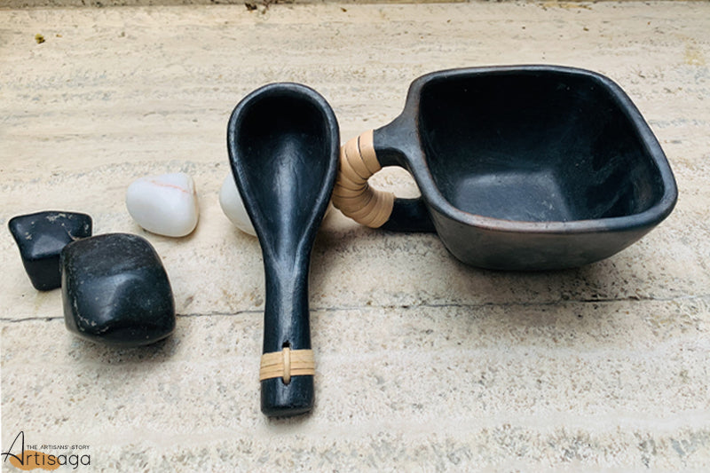 An eco-friendly earthenware clay soup bowl with a spoon of Longpi pottery from Manipur.   From being smooth on the interior to the exterior, this square shaped masterpiece is handcrafted by an artisan to meet the user's eye. The black clay is complemented well with the beige cane details. The wide mouth of the bowl along with the spoon makes it easy to sip on hot soup.