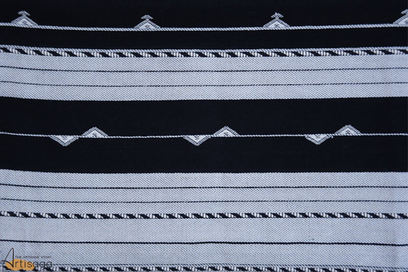 A traditionally hand woven 100% cotton stole from Kutch, Gujarat.   An intricately hand woven stole of the Kutch community brings forward the cultures and beliefs of the populace. The parallel stripes woven with the help of solidified black and white pigment gives it a very sophisticated yet casual aura. Geometric motifs woven along with traditional kachchhi border with a brink of tassels completes the overall look of the product. A classic and hand woven piece must have in everyone's wardrobe.