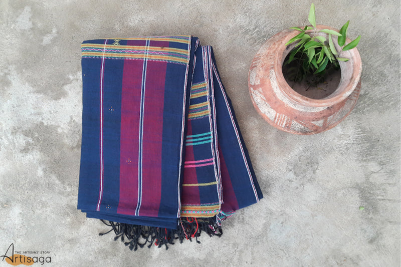 A traditionally handcrafted cotton saree from Kutch, Gujarat.   The unique colour combination of sky blue, pink and yellow on navy blue makes this saree one of a kind. The intricate detailing with traditional Tangalia motifs, 'tree of peacock' throughout the saree brings forward the various cultures and beliefs of this community. The miri border along with the playful tassels complement the overall look of the saree. This casual yet classy piece is suitable for all kinds of occasions.