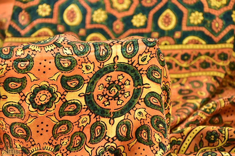 An ornate hand block printed modal dupatta from Ajrakhpur, Gujarat.   This beguiling mustard dupatta is hand block printed with traditional floral and minari motifs of Ajrakh. The entire dupatta is a delight to the viewer's eye because of the use of complimentary green and yellow bordered floral vines. The dupatta can be styled with every classic ensemble of your wardrobe.