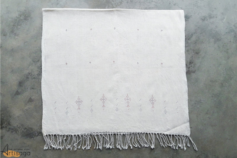 A traditionally handcrafted 100% organic cotton stole from Kutch, Gujarat.   This simple stole is handcrafted by the diligent artisans of Kutch, Gujarat. The stole has intricate dana motifs along the length of the stole. The edges have minute and delicate red coloured geometric motifs, traditional to the Tangalia weaving style. This classic stole with its playful tassels is a must have in your wardrobes.
