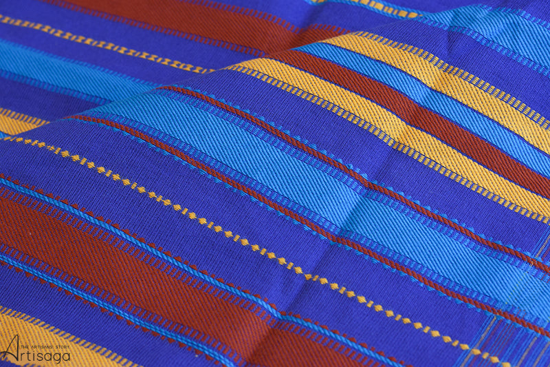 A traditionally hand woven 100% cotton stole from Kutch, Gujarat.   This flamboyant handcrafted stole with a vivid colour combination of blues, yellow and sienna, gives a sumptuous feel to the wearer. The ends of the stole woven with colourful stripes add liveliness which is further embellished with delicate tassels. This elegant and stylish stole can be layered with any outfit of your choice.