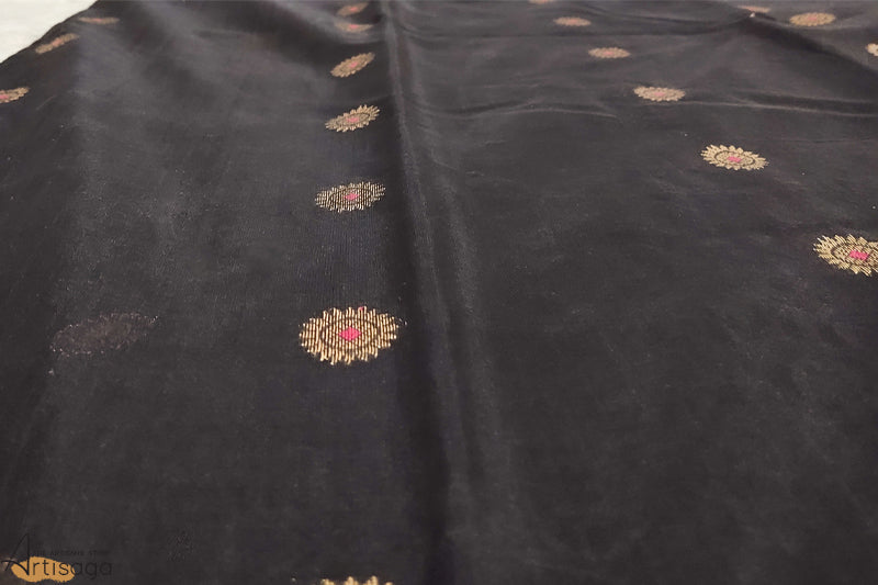A diligently hand woven Chanderi cotton silk saree from Madhya Pradesh.   A contemporary touch is given to this traditional hand woven chanderi saree with black being a dominant colour. It radiates confidence as the golden and pink border perfectly complements the saree. The work is done diligently to preserve its contemporary feel. Style this piece well with honour and pride.