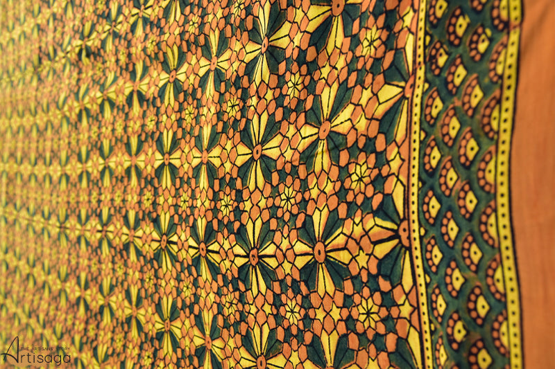 An enchanting hand block printed modal saree from Ajrakhpur, Gujarat.   Simplicity blended with precision and technique is the unique selling point of this hand block printed saree. The colours yellow, orange and green completely complement one another on the shade card hence look so majestic when printed as traditional motifs of Ajrakh. The magic is enhanced by the zari border at the pallu. Give this saree a contemporary look by pairing it with an emerald green shirt and rustic golden earrings.