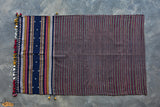 An intricately hand woven 100% cotton stole from Kutch, Gujarat.   Parallel violet and grey stripes complement each other with utmost precision. The piece consists of variations of miri (like braided) borders. The wide dark blue stripe along with chaumukh motif add depth and elegance to the stole. Layer it over a kurti, oxidized jewellery and jutis for a traditional look.