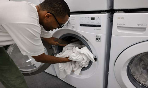 putting clothes in washer