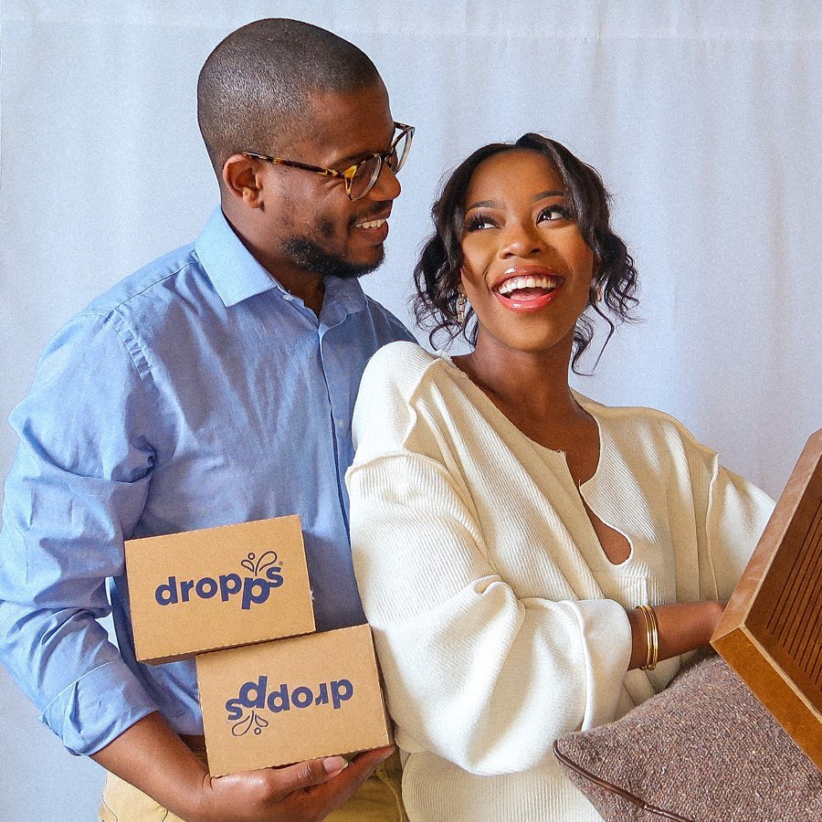 Young couple holding two boxes of Dropps
