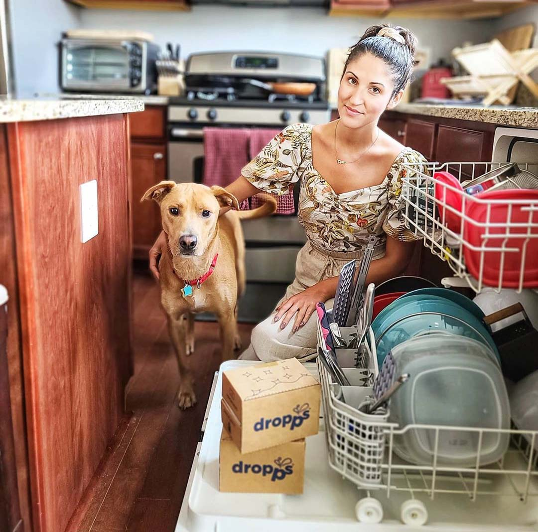 Woman and her dog doing loading a dishwasher with Dropps