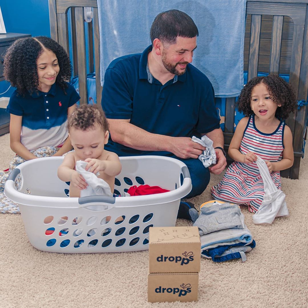 Father and three children folding laundry with Dropps