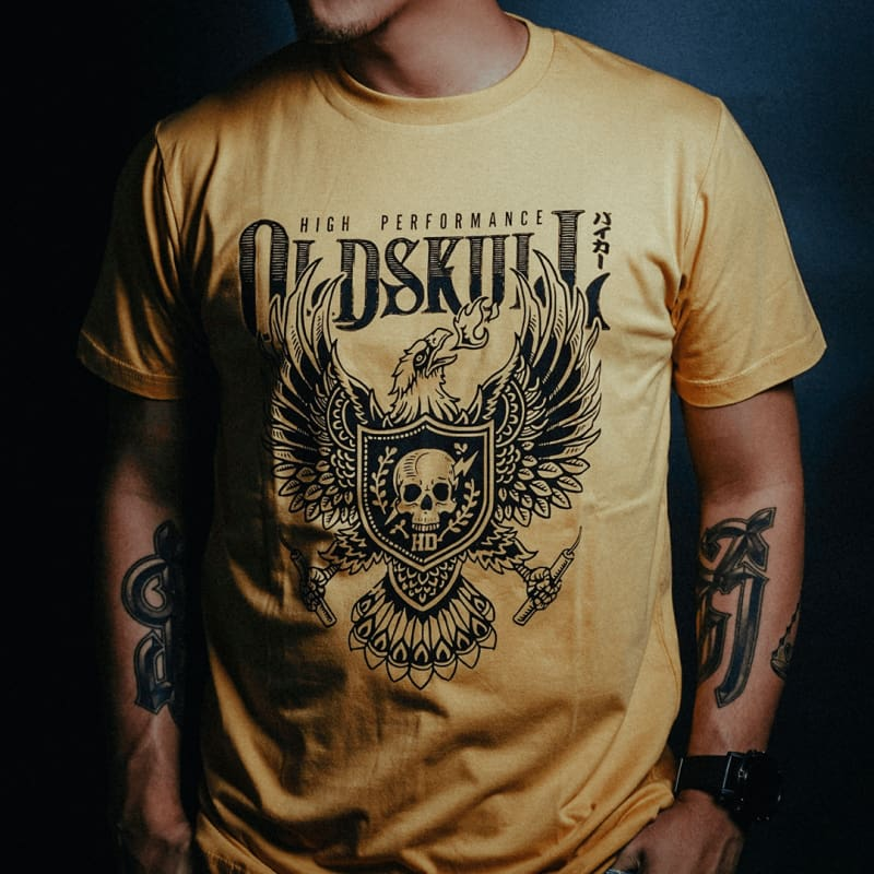 This shirt comes in yellow gold, black or white.  It has a eagle emblem with a shield in the center containing a skull with lightning through it.  The brand name Oldskull Shirts is written above it in bold print.  This is a streetwear vintage style of shirt made of the coolest design.