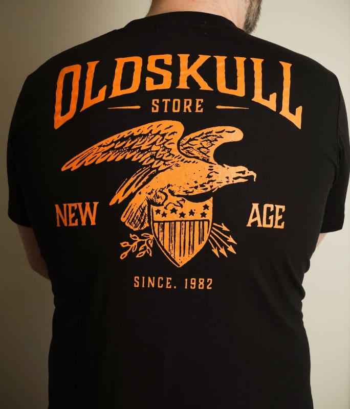 This shirt is similar to the Harley Davidson style of shirts.  It is black with orange print.  It has a small Oldskull Shirts logo on the front.  On the back it has an large eagle over a shield design with the words Oldskull Store written over it.  It is a vintage streetwear design.